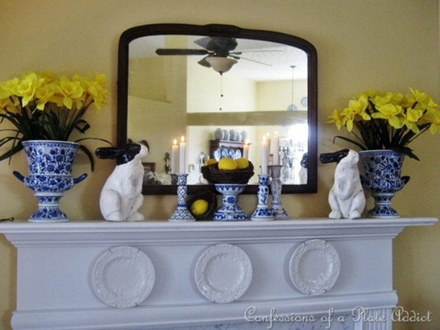 a bright Easter mantel with fake bunnies, yellow daffodils in blue and white pots and candle holders