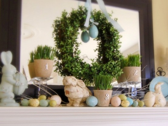 pastel eggs, bunny figurines, potted grass and a greenery wreath with an egg
