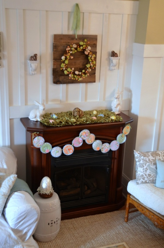 a cute Easter mantel with a pastel egg wreath, a moss decoration with pastel eggs and a vintage paper bunting