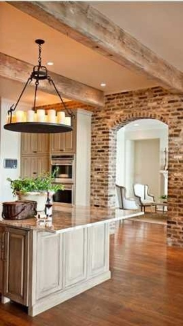 distressed brick walls and wooden beams on the ceiling bring texture and interest to the kitchen making it more rustic