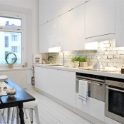 sleek white cabinets are complemented with a white brick backsplash and a white wooden floor that add texture to the space