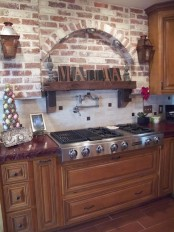 red brick walls paired with rich stained traditional furniture create a welcoming and cozy vintage kitchen