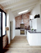 a red brick wall and white wooden cabinets bring in texture and contrast with each other