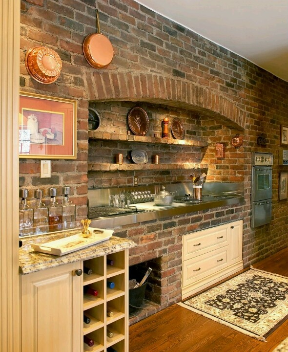 an original brick wall exposed sets the tone in the kitchen making it industrial, vintage and rustic at the same time