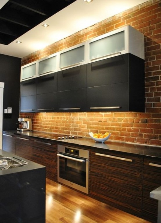a red brick wall adds texture and color to the space and contrasts the sleek cabinets
