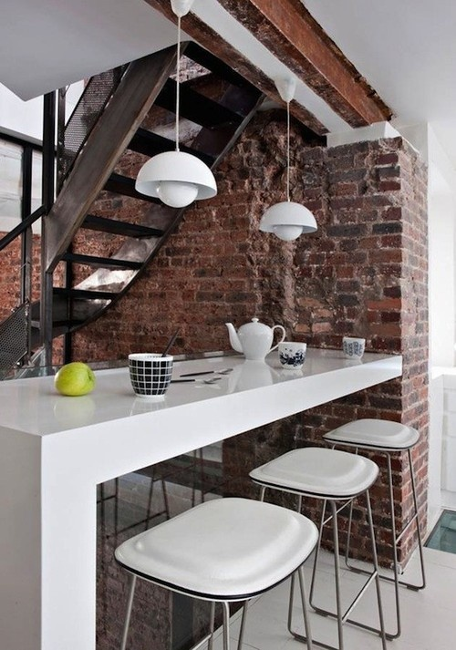 an exposed red brick wall in the eating space brings texture, interest and contrasts the sleek white furniture