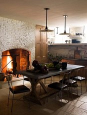 a large fireplace clad with white brick and a concrete table make up a cool space and add texture to the space