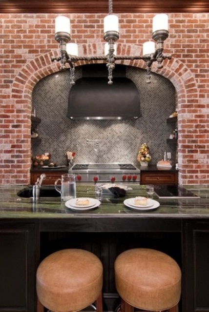 a red brick wall contrasts the grey tiles and a green stone countertop and add colro to the space