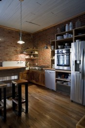 red brick walls match the rich stained wood and add texture and interest to the kitchen