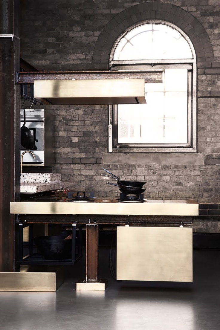 a taupe brick wall makes the luxurious kitchen less formal and more relaxed at the same time