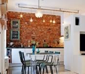 a red brick statement wall stands out in a sleek white kitchen and adds color and texture to the space