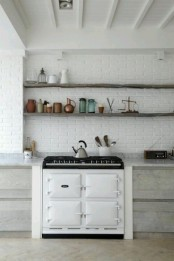 a white brick wall adds texture to the space and matches the neutral kitchen decor at the same time