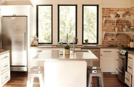 red bricks, shiny metal surfaces, simple white cabinets make up a stylish rustic meets industrial kitchen