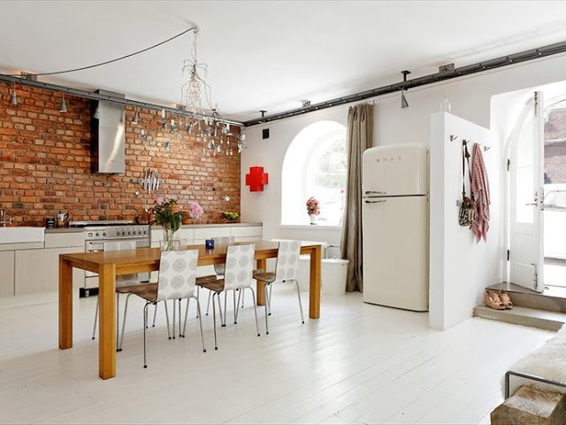 a bright white kitchen is spruced up with a red brick wall that adds interest to the space and makes it more color filled