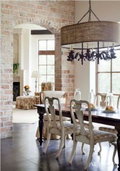 exposed red brick walls in the dining room add texture and make this refined space less formal and more relaxed