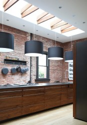 a red brick wall and rich stained wooden cabinets for a masculine feel in the kitchen and black pendant lamps over it