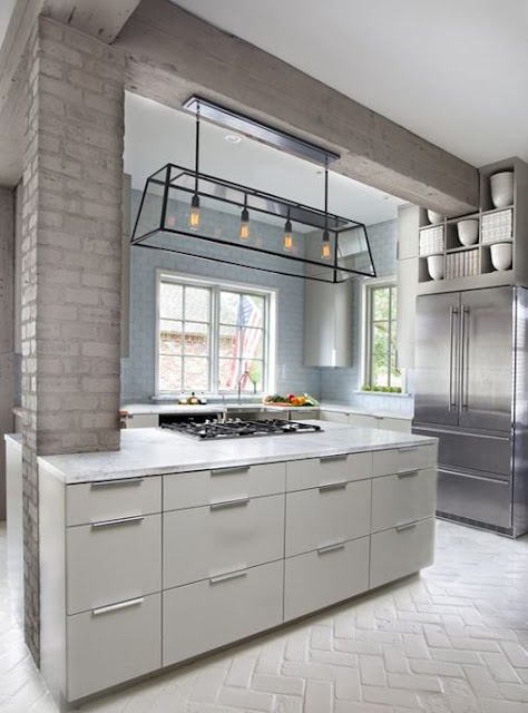 light blue brick walls and a taupe brick pillar complete the space adding subtle touches of color to the kitchen