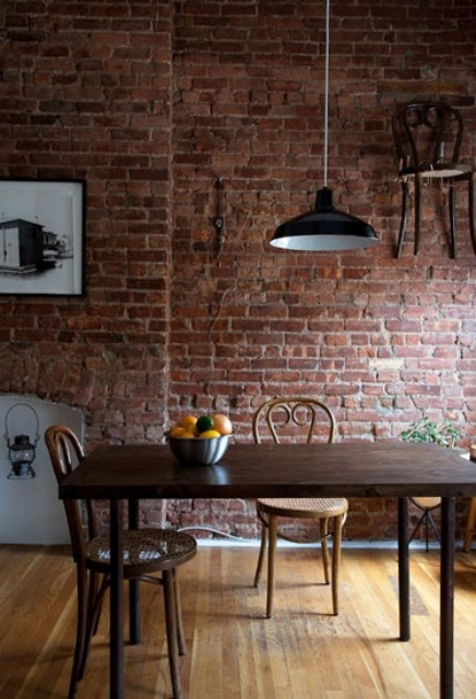 an exposed red brick wall and dark stained wooden furniture for a bold and chic dining space with an industrial feel