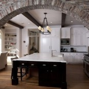 an exposed brick arched doorway adds texture to the space and makes it bolder and more chic