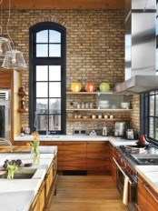 neutral exposed brick walls paired with amber wooden cabinets for a chic and bright kitchen with double height ceilings