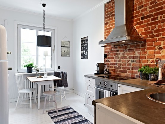 an all-white kitchen with a red brick cooker backsplash that adds interest, color and even character to the space