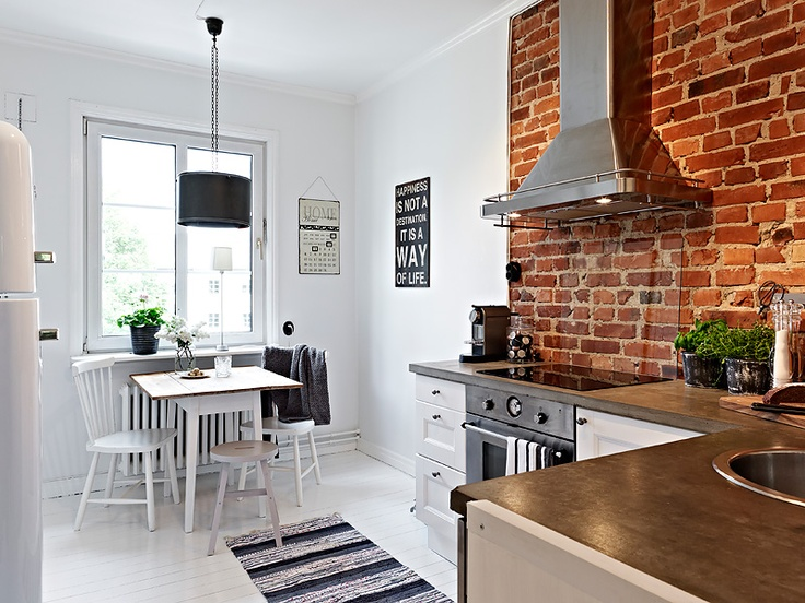 an all white kitchen with a red brick cooker backsplash that adds interest, color and even character to the space