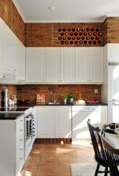 vintage white cabinets and red bricks contrast with each other and add texture to the kitchen