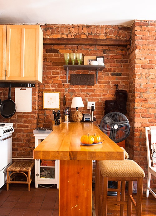 a red brick wall and light stained wooden furniture make up a cozy warm colored dining nook