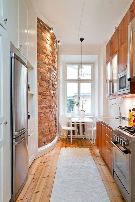 a modern kitchen done in white with with sleek plywood cabinets that echo with the curved red brick wall