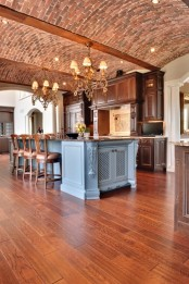 an arched red brick ceiling with wooden beams and rich stained wooden cabinets create a gorgeous space with an elegant vintage feel