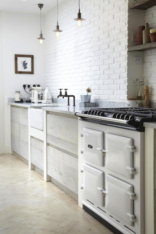 a white brick wall perfectly matches the Nordic kitchen and adds texture and interest to it