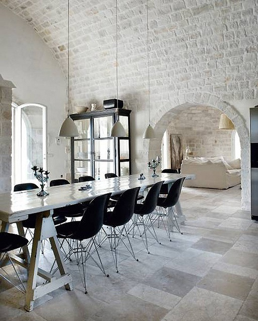 white brick going from the walls to the arched ceiling look bold with contemporary furniture in black creating an eclectic look