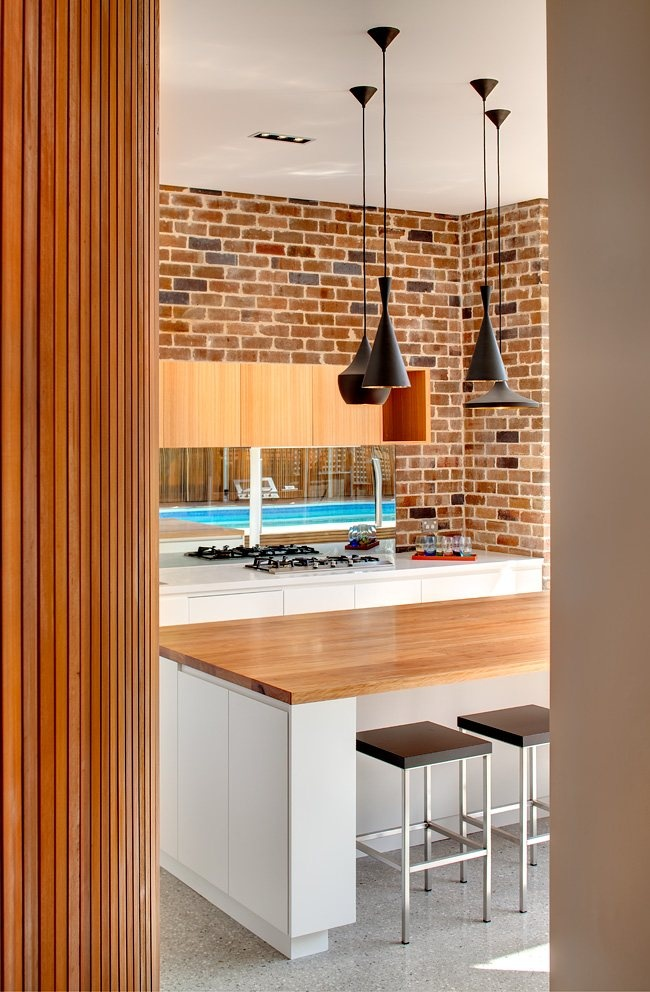 a brick wall makes the sleek modern space more relaxed and rustic and adds texture to it