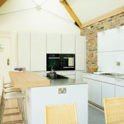 sleek white cabinets contrast the red brick wall that makes them stand out even more