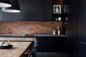 a moody black kitchen with a red brick backsplash that enlivens the space and makes it bolder and cooler
