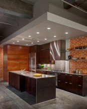 a dark modern kitchen with a red brick wall and rich stained wooden furniture for a catchy and bold look