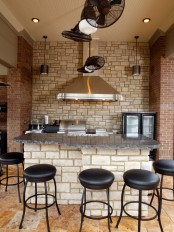 a faux stone wall and red brick pillars on each side make the kitchen bolder and bring a textural touch