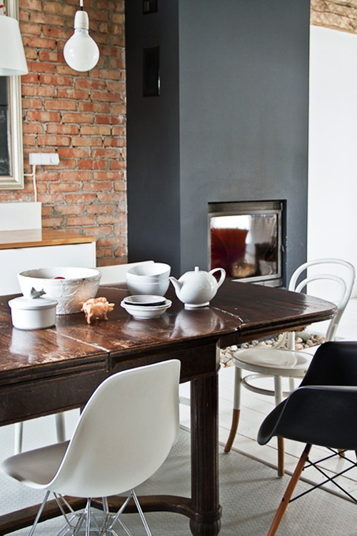 a red brick wall and a matte black hearth next to it to create a bold contrasting look that takes over the space