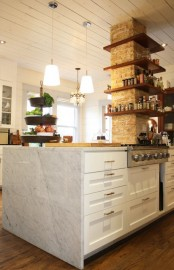 a brick pillar with wooden shelves is a catchy decor element that adds texture and storage space to the kitchen