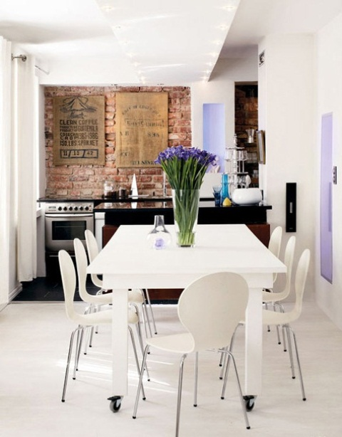 an eclectic kitchen in white and lavender with a red brick backsplash as a bright textural element