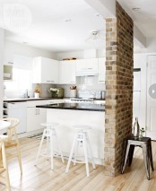 a red brick pillar separates the kitchen from the next space adding interest and texture to both