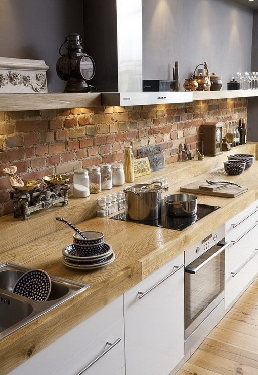 a red brick backsplash contrasts the neutral wooden countertops and white cabinets and makes the kitchen catchy