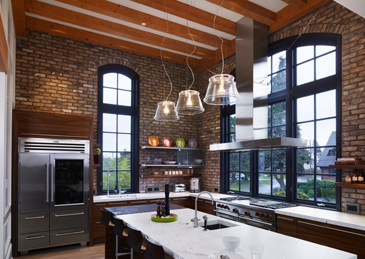 a dark kitchen with red brick walls and arched windows plus refined rich stained furniture