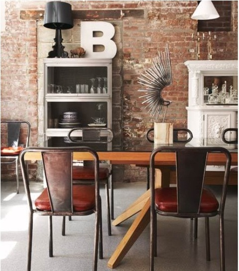 a distressed red brick wall in the dining zone and metal chairs mix up with refined and contemporary furniture for a unique look