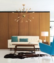 a simple and neutral living room with a plywood covered wall, a sunburst chandelier, a creamy sofa and a blue chair plus matching pillows