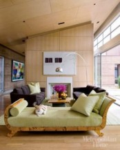 a bright mid-century modern living room with plywood walls and ceiling, dark furniture and a green couch with lots of pillows