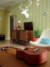 a mid-century modern living room with green printed wallpaper, elegant dark stained furniture and a faux animal head