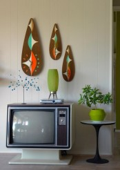 bright plywood artworks and clocks, potted greenery, vases and a retro TV to add a real retro touch to the living room