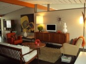 a neutral living room with touches of orange and amber plus elegant warm-colored stain on the furniture