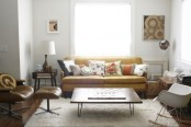 a neutral living room with mid-century modern furniture, artworks and a leather chair plus bright pillows
